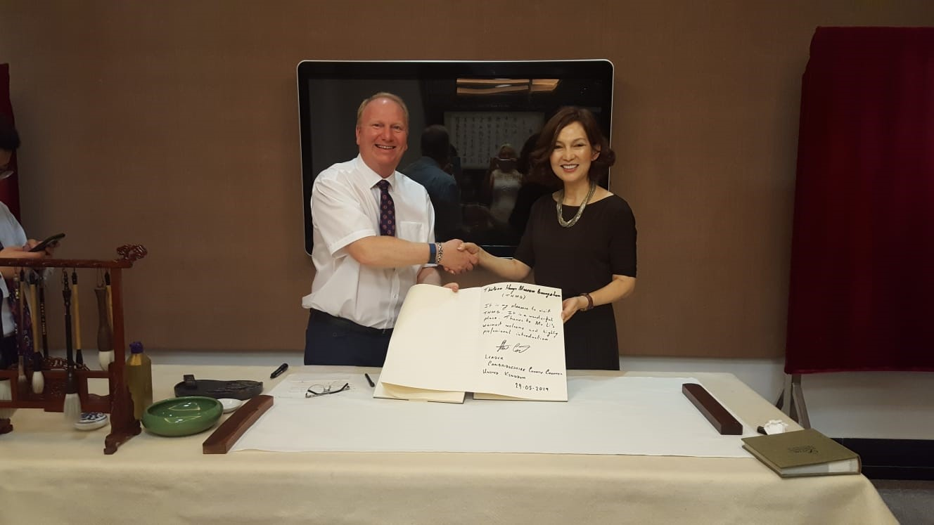 Cllr Steve Count signing a visitors book with Chinese entrepreneur Miss LiLi at her museum.